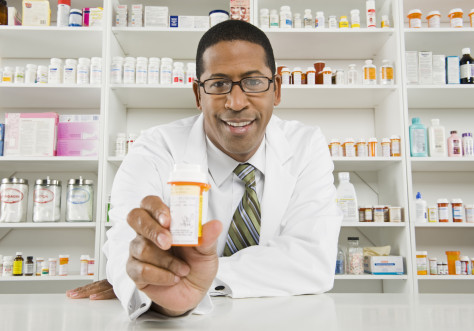 Portrait of a happy African American pharmacist prescribing medicine at workplace